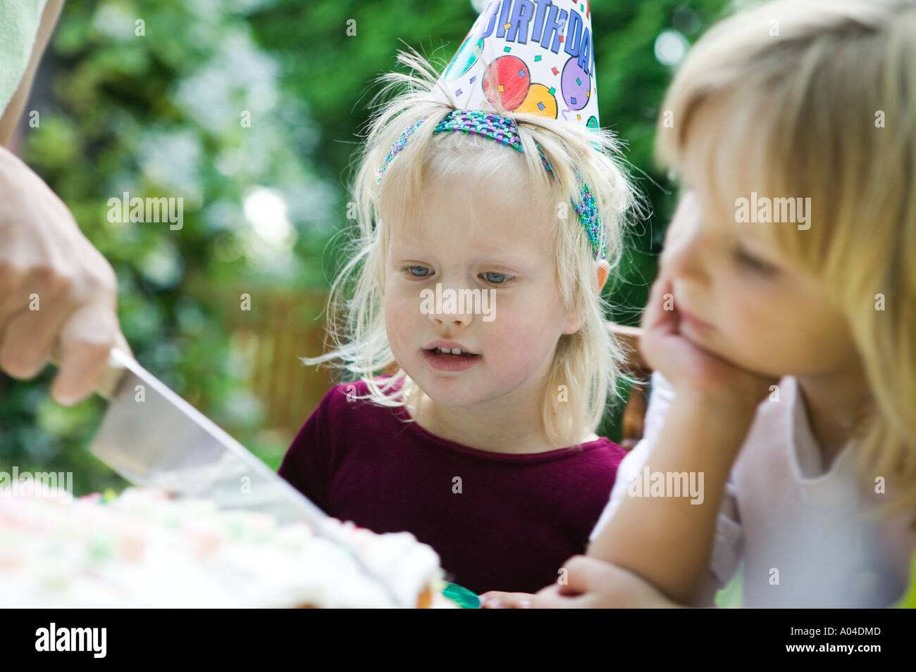 Anno Vecchio girls watching torta di compleanno il taglio Immagini Stock