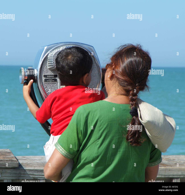 Clearwater Beach.Pier 60 donna asiatica e il bambino guarda verso il mare.a lungo raggio macchina binoculare. Immagini Stock