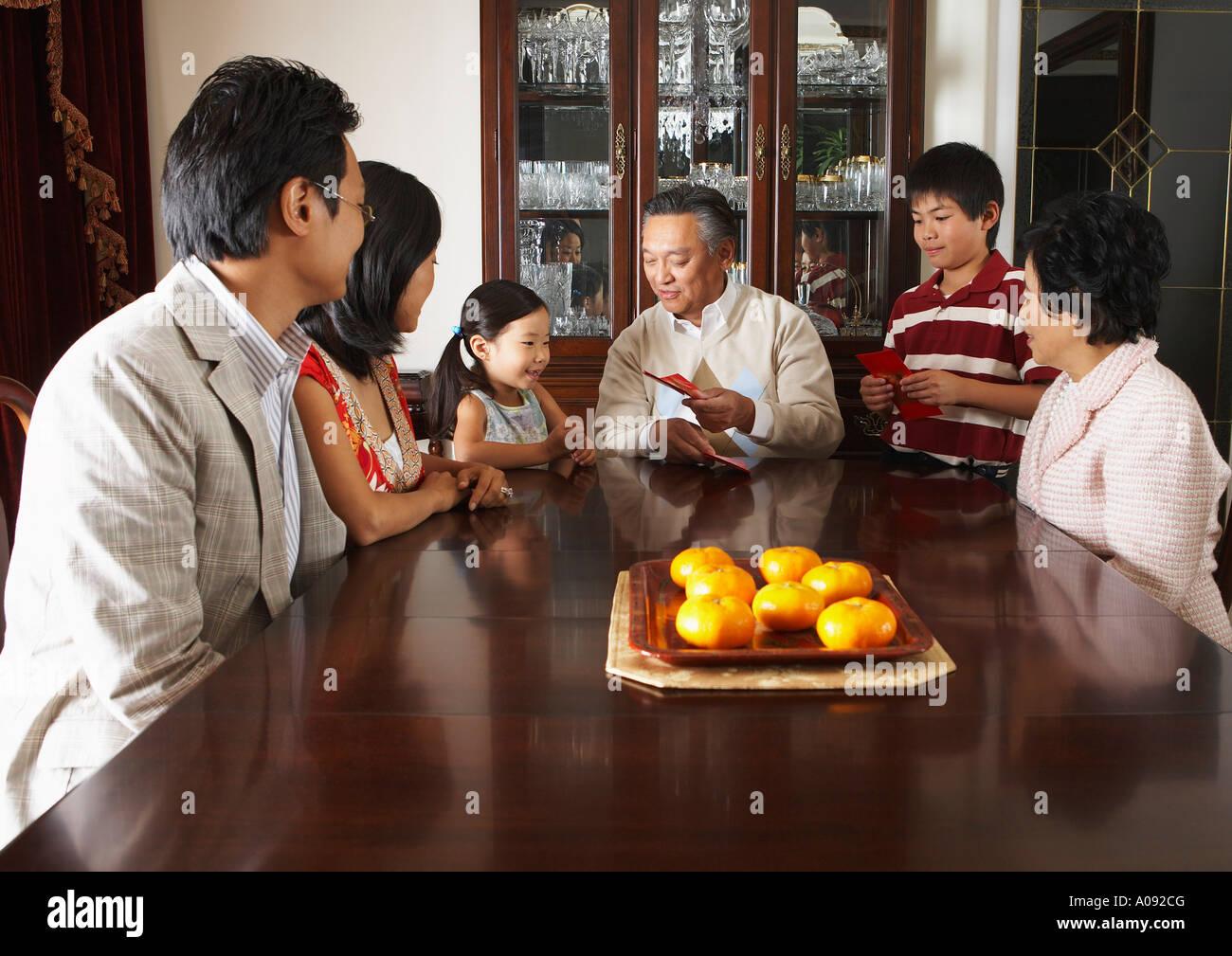 Famiglia Seduti Attorno Al Tavolo Da Pranzo Foto Stock Alamy