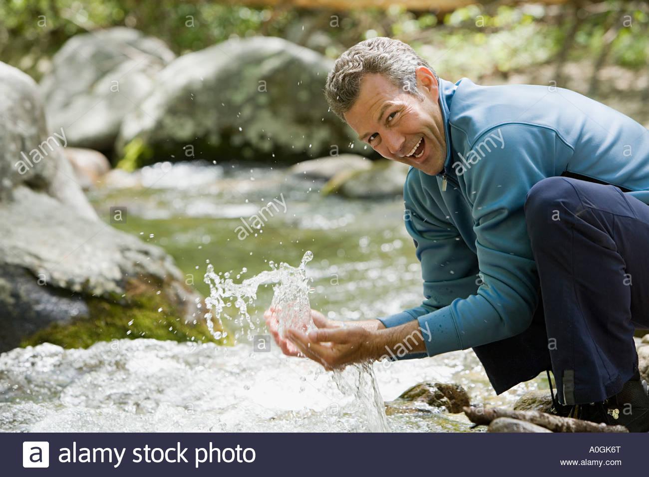 L uomo stesso rinfrescante in un flusso Immagini Stock