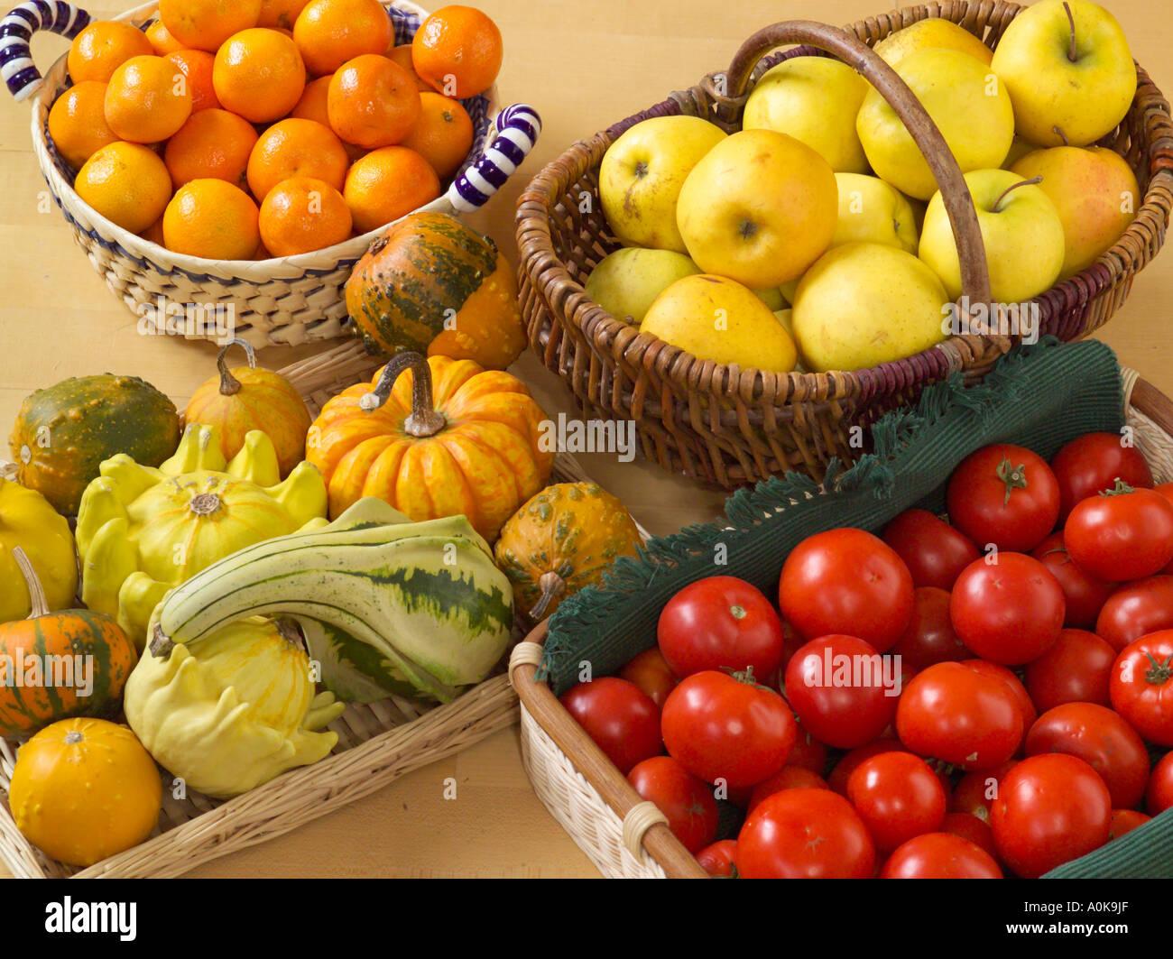 Tangerini mele zucche e pomodori in cestelli Immagini Stock