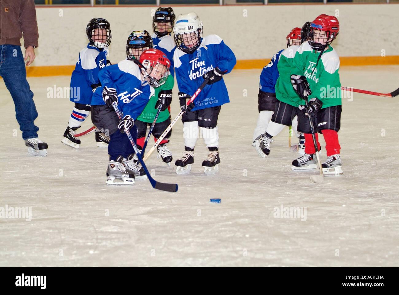5 anno di età i ragazzi e le ragazze stanno imparando i fondamenti di giocare a hockey su ghiaccio Immagini Stock