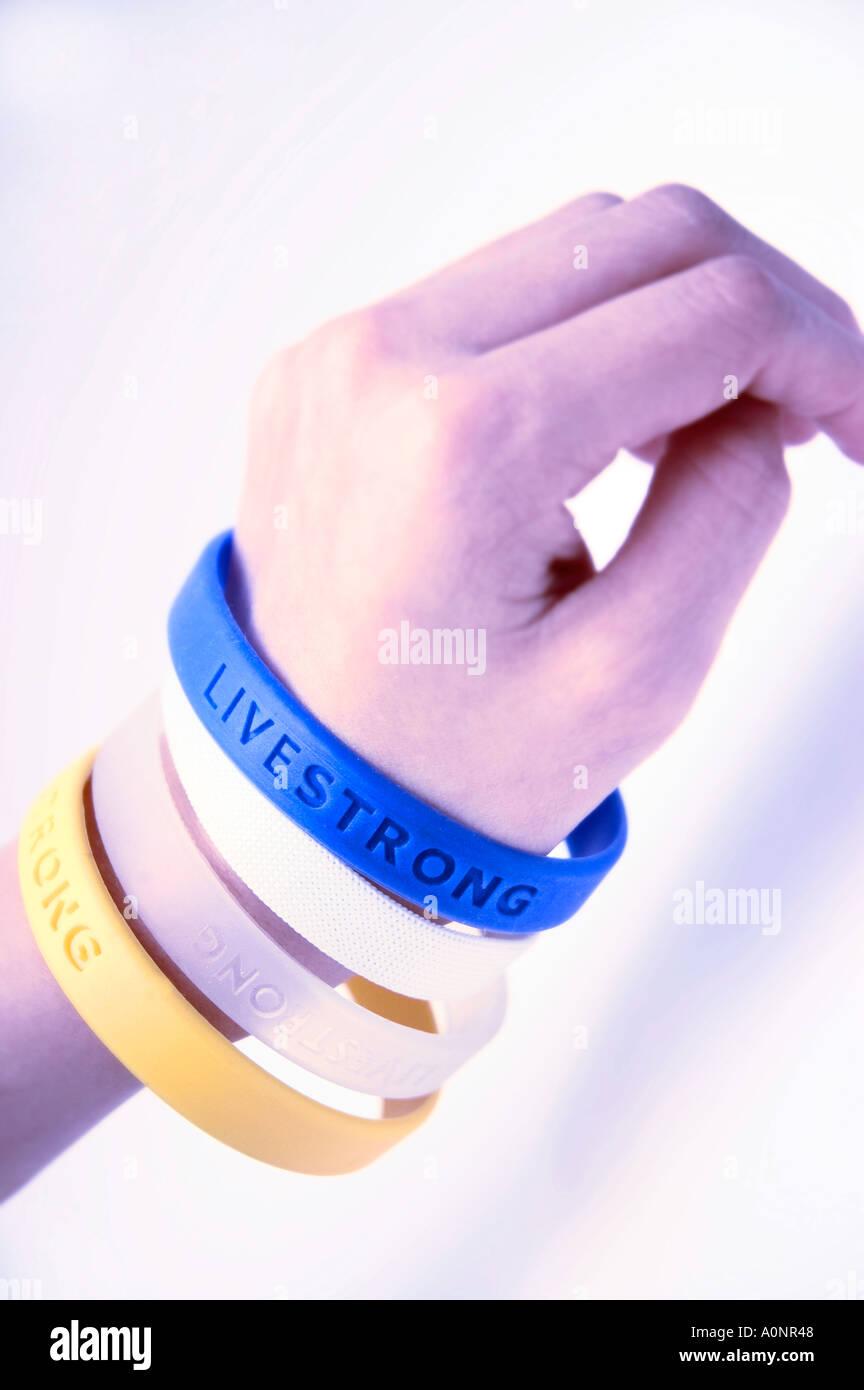 Alla moda di gomma Livestrong fascia braccio bracciali su un braccio childs Lance Armstrong Foto Stock