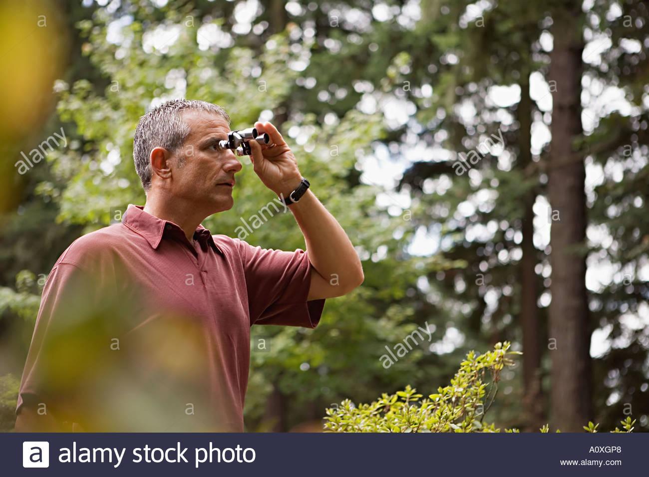 L'uomo con un binocolo in foresta Immagini Stock
