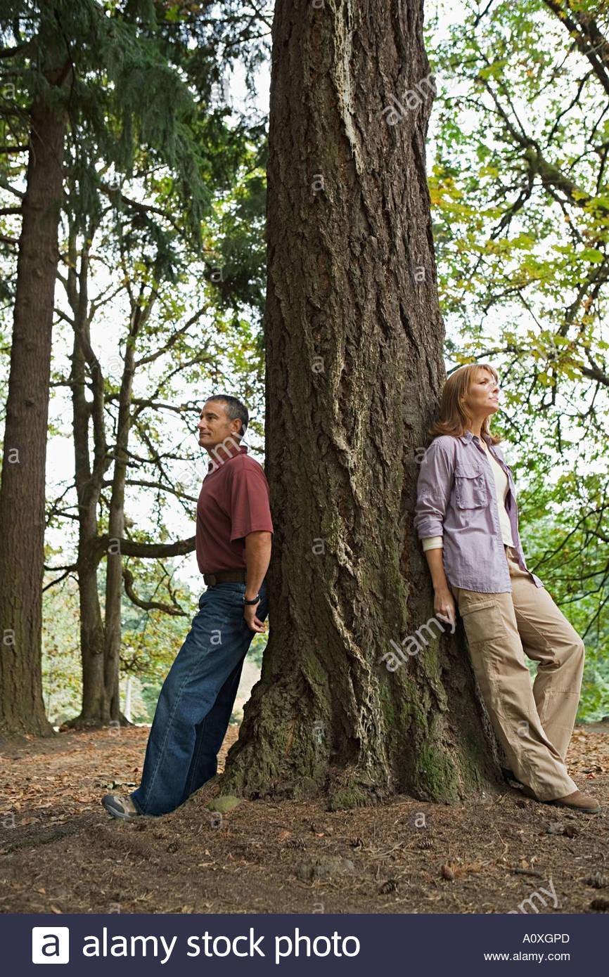 L uomo e la donna appoggiato su una struttura ad albero Immagini Stock