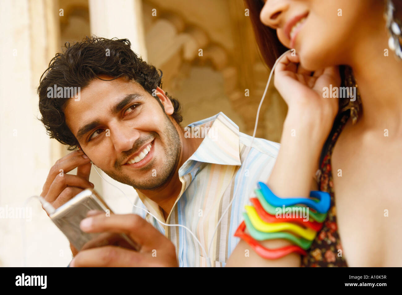 Close-up di una giovane coppia ascoltando musica su cuffie, al Forte di Agra, Agra, Uttar Pradesh, India Immagini Stock