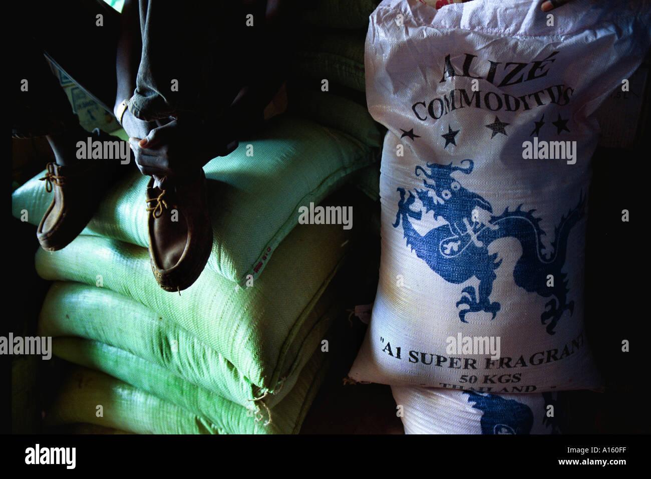 Un commerciante senegalese si siede sulla parte superiore dei sacchi di riso Asiatico che vendono per meno di riso locale in un mercato in Africa occidentale Immagini Stock