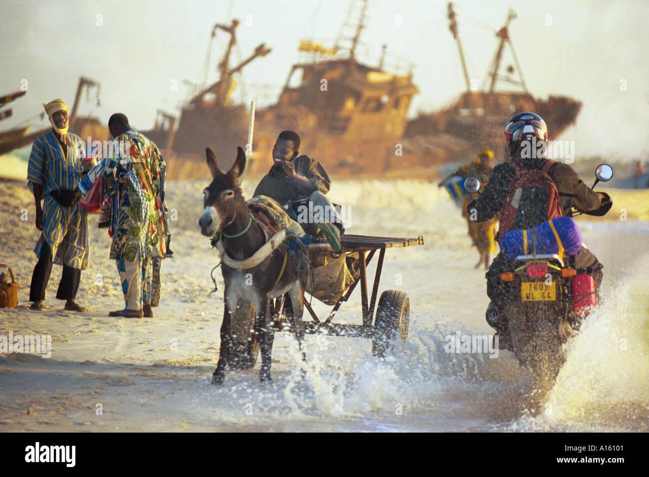 Un ragazzo con un asino per il trasporto di pesce per il mercato locale è schizzato da una moto sulla costa della Mauritania dove local Immagini Stock