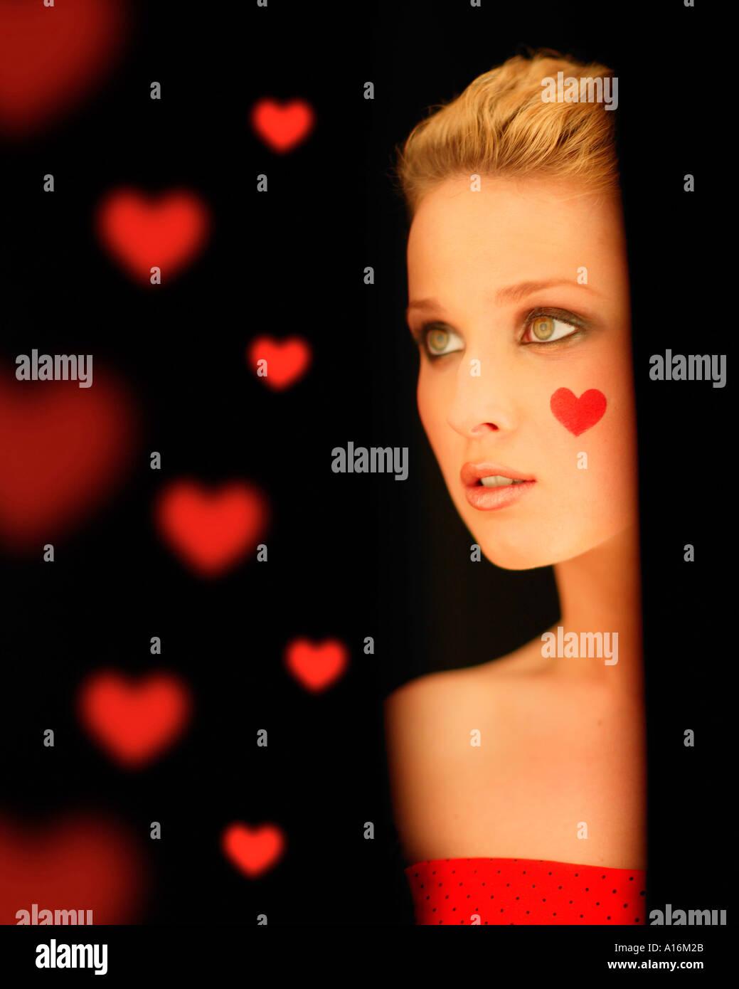 Ritratto di giovane donna 18, 19, 20, 21, 20-24, 24-29, 30-34, anni con cuore rosso dipinto sulla guancia Foto Stock