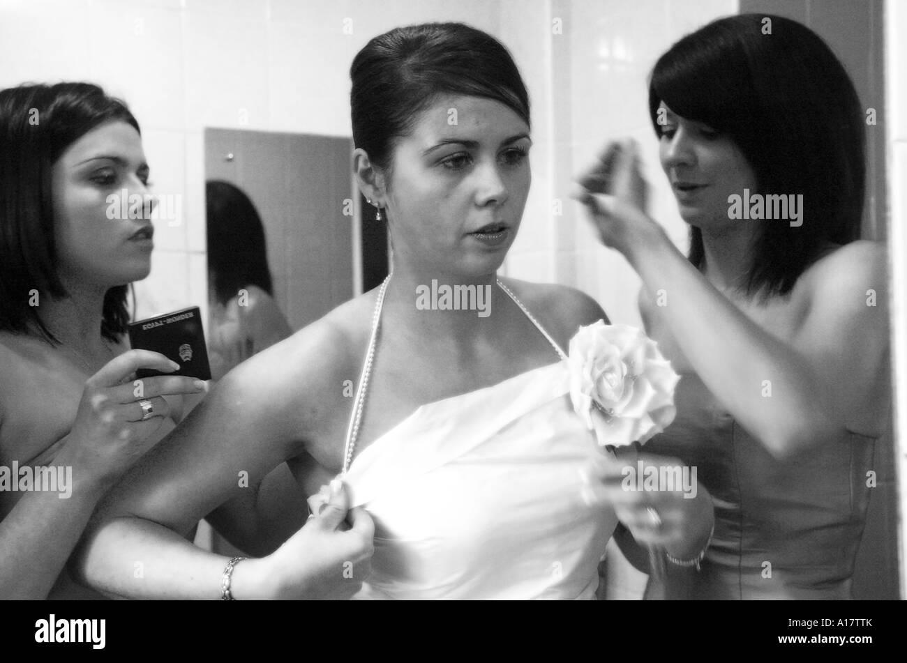 Una sposa guardando nello specchio ottenere pronto per il grande giorno con  l aiuto delle sue ca582ed7422f