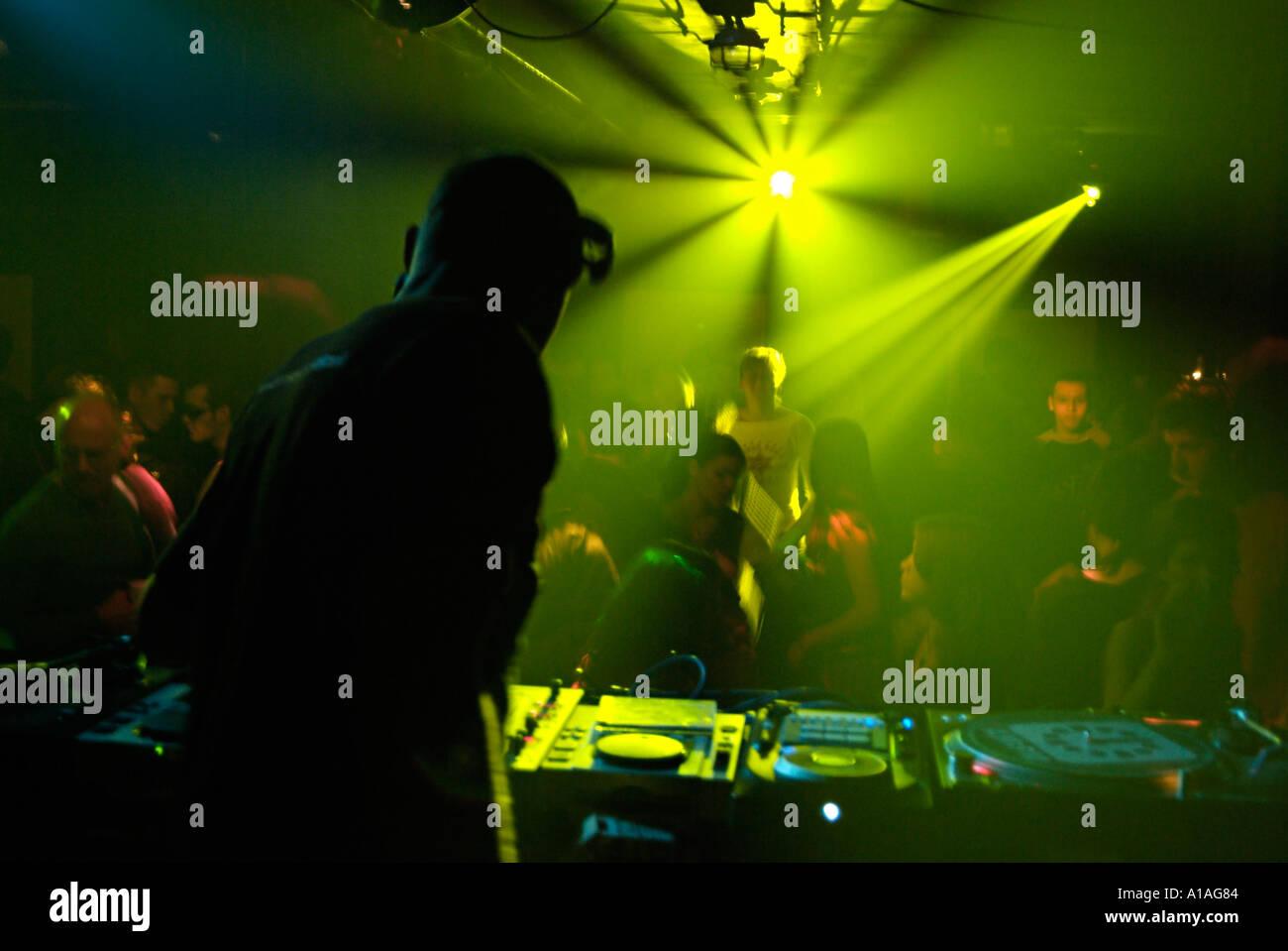 Club DJ dietro i ponti di un Nightclub affollato. Immagini Stock