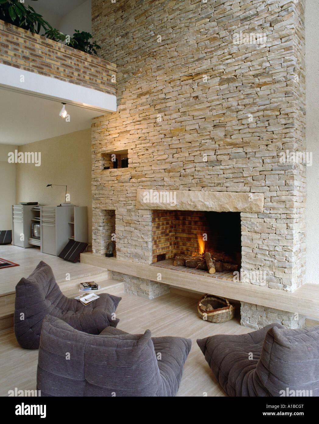 Acceso il fuoco nel camino in pietra parete del fienile conversione, con moderne poltrone di ...