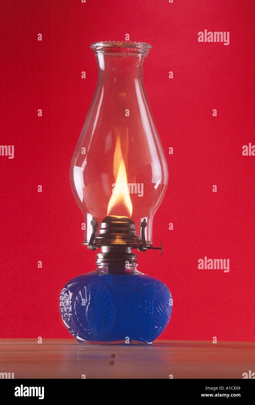 Ancora la vita di vetro spia dell'olio con fiamma blu e olio in taglia base di vetro sfondo rosso PR CL Immagini Stock