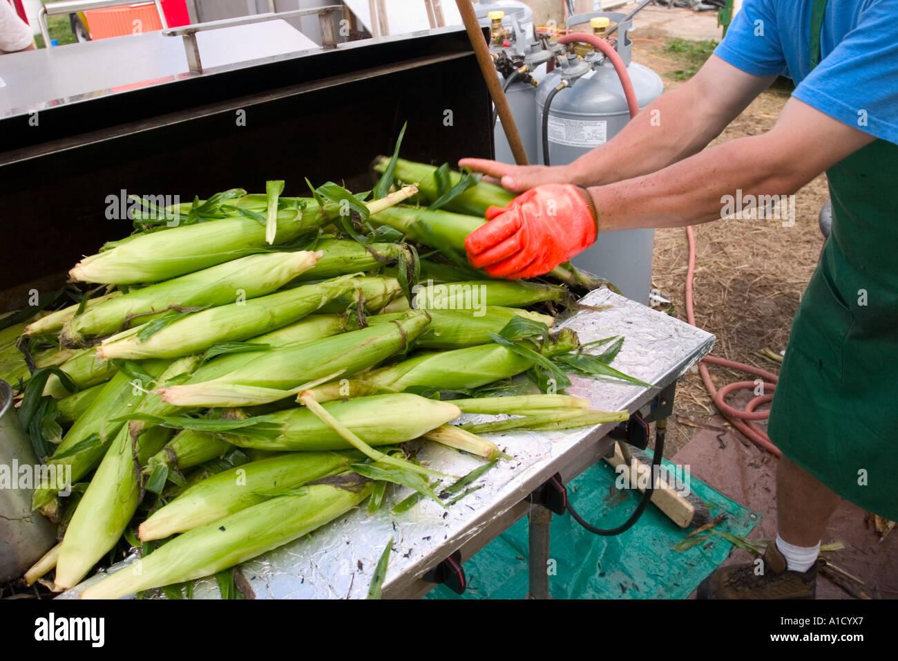 Fornitore maschio preparazione del mais per grigliare a una fiera in Connecticut USA. Immagini Stock