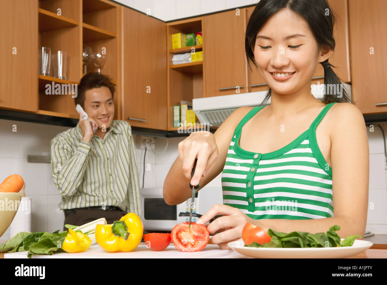Close-up di una giovane donna di tagliare le verdure in cucina con un giovane uomo che parla su un telefono cellulare Immagini Stock