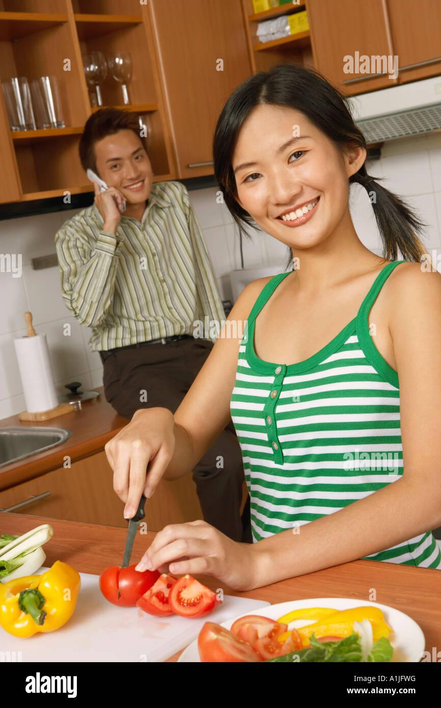 Ritratto di una giovane donna di tagliare le verdure in cucina con un giovane uomo che parla di un telefono cellulare Immagini Stock