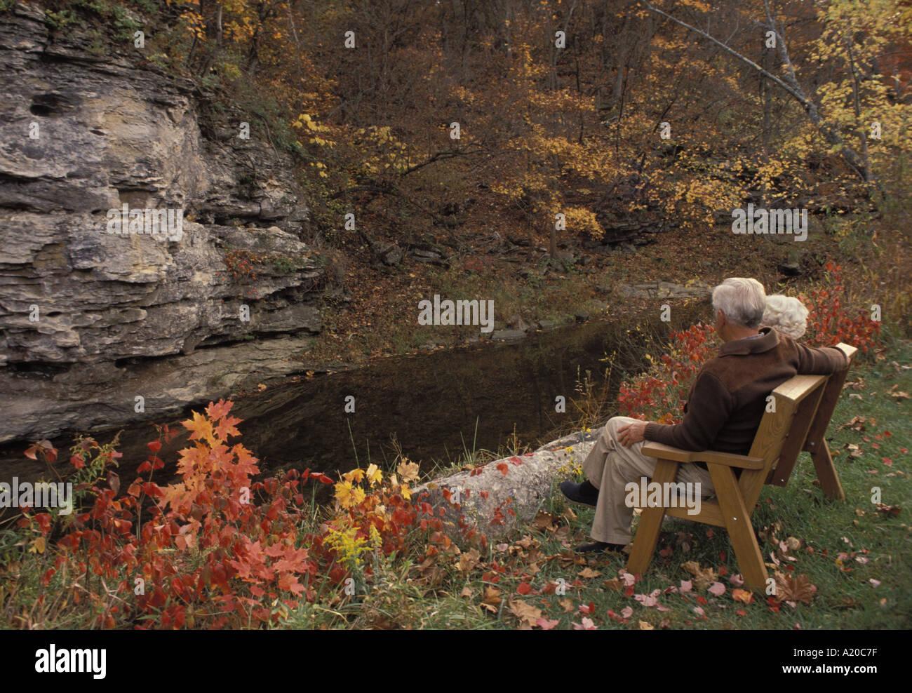 Coppia senior godendo di una caduta di sera su un banco da creek e alte scogliere Midwest USA Immagini Stock
