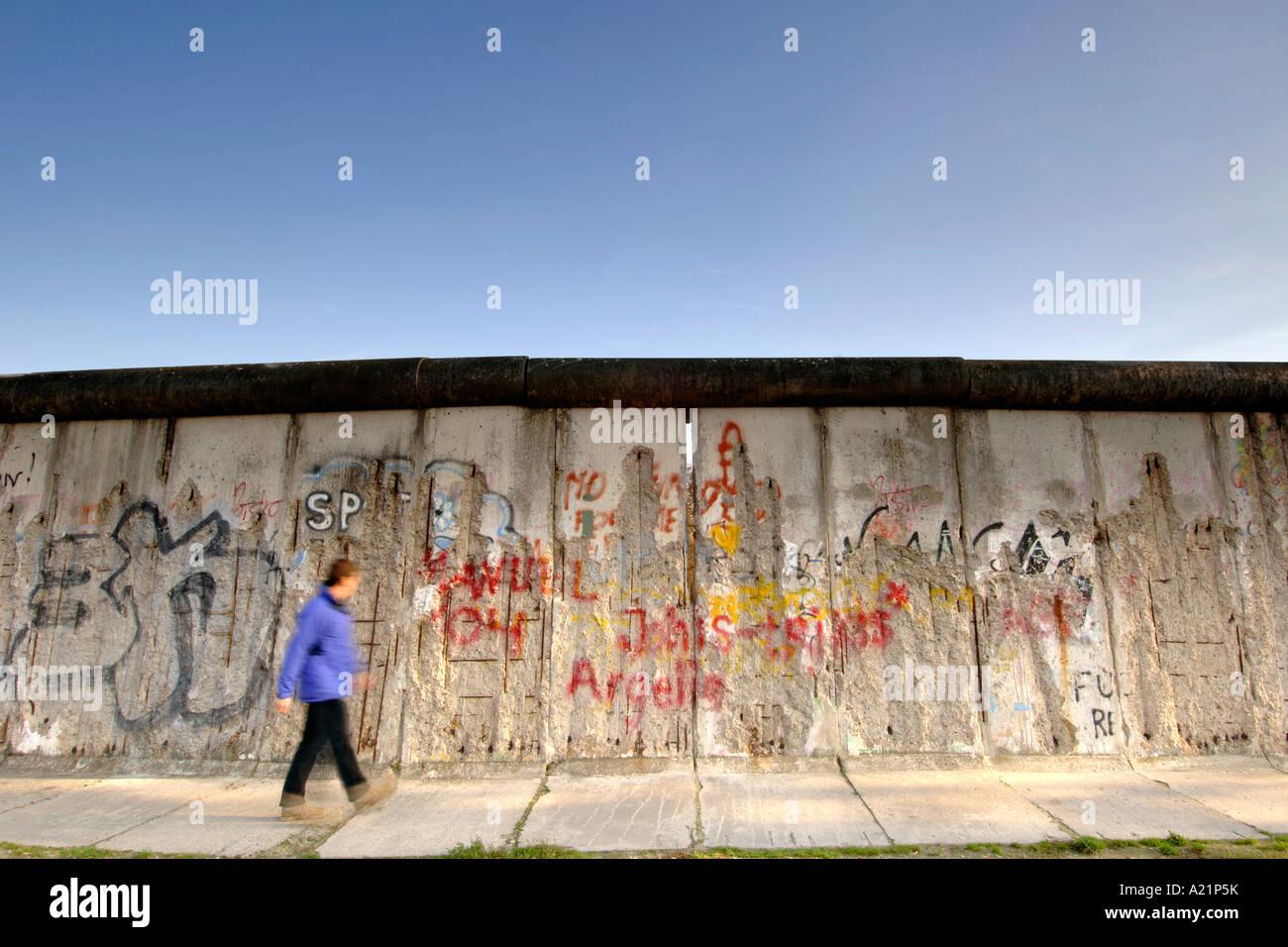 Un uomo cammina oltre il muro di Berlino lungo Bernauer Straße a Berlino Est della Germania. Immagini Stock