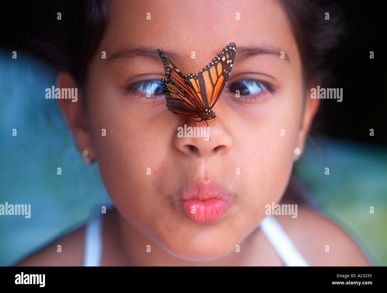 Un giovane bambino guardando una farfalla monarca sul naso con gli occhi incrociati bocca Pursed Sandra Baker Immagini Stock