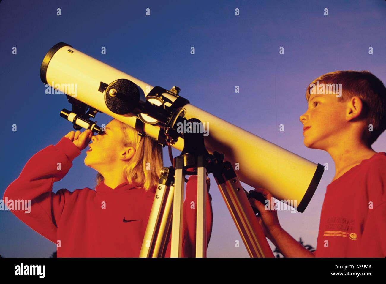 Dieci anni e fratello di undici anni suor osservare le stelle attraverso il telescopio di Santa Barbara in California Immagini Stock