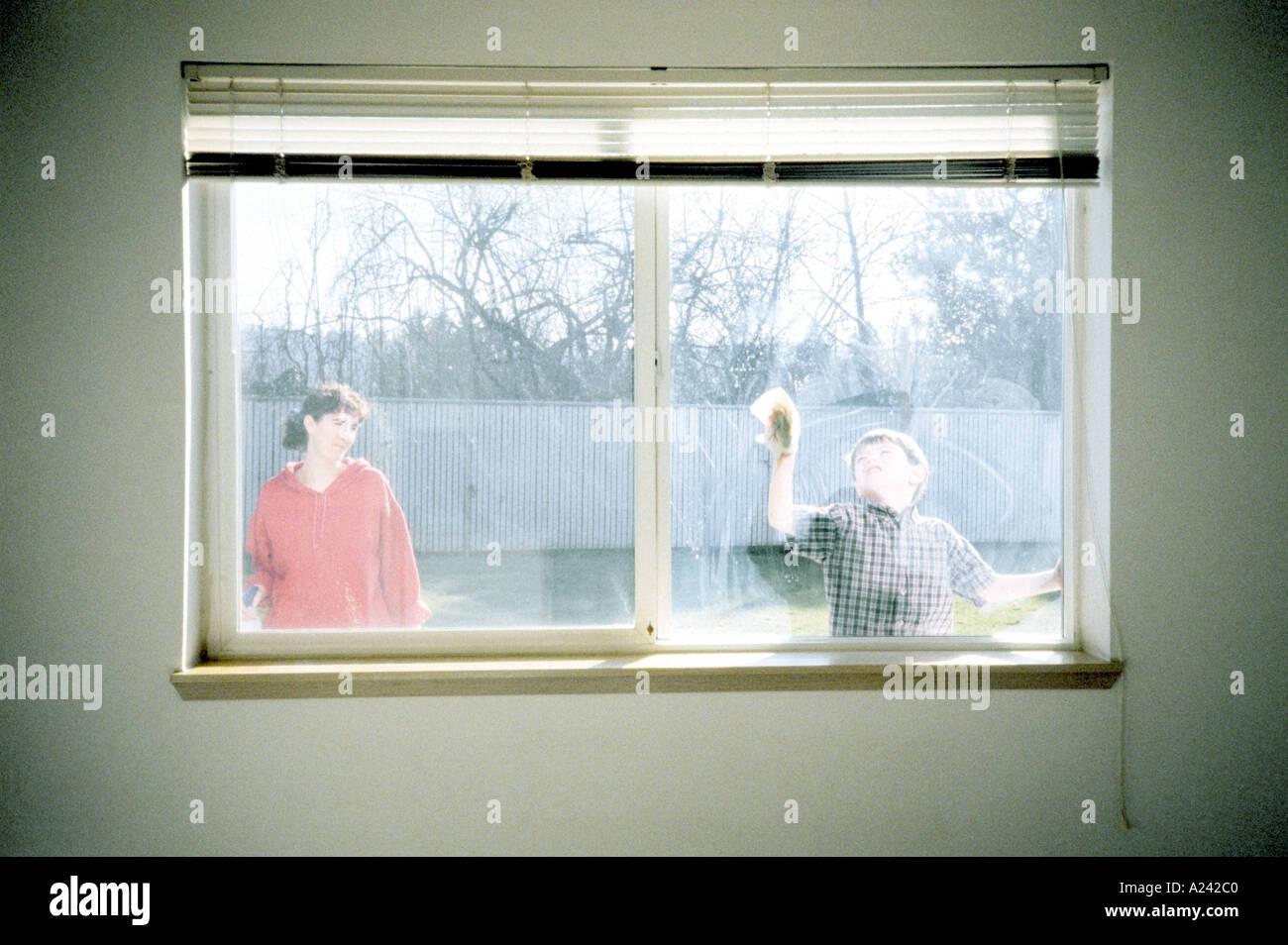 Guardare la madre figlio lavare window vista dall'interno di casa Immagini Stock