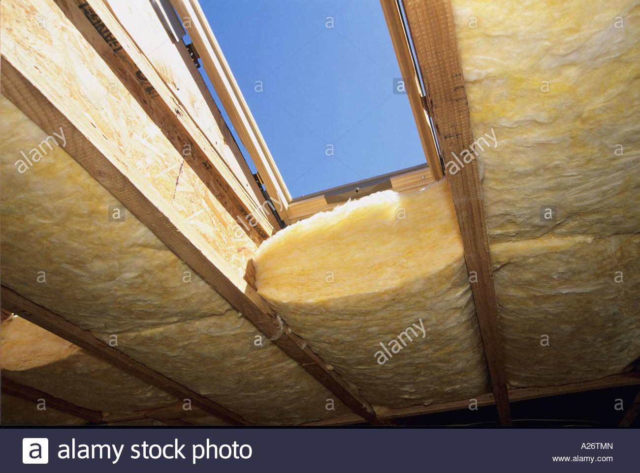 R38 isolamento in fibra di vetro che viene installato nel tetto nuovo stile loft home in costruzione Foto Stock