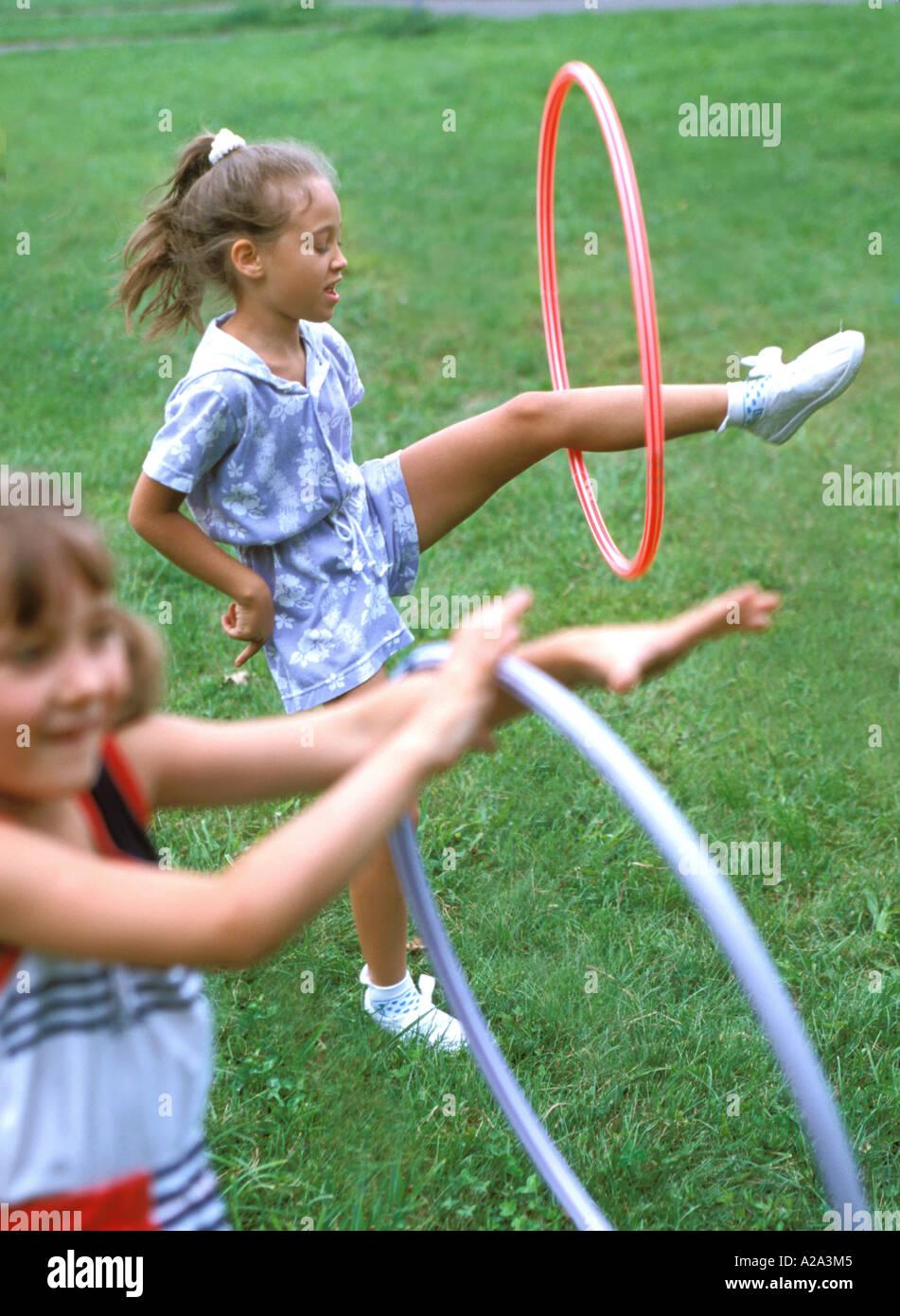 Le ragazze la filatura hula hop sulla gamba MR8417 7A Immagini Stock