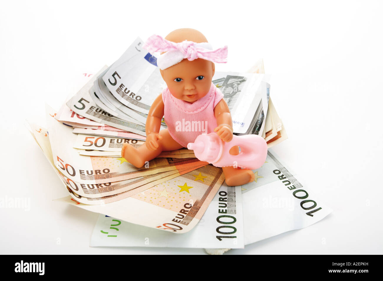 La bambola seduta sulle banconote in euro Immagini Stock