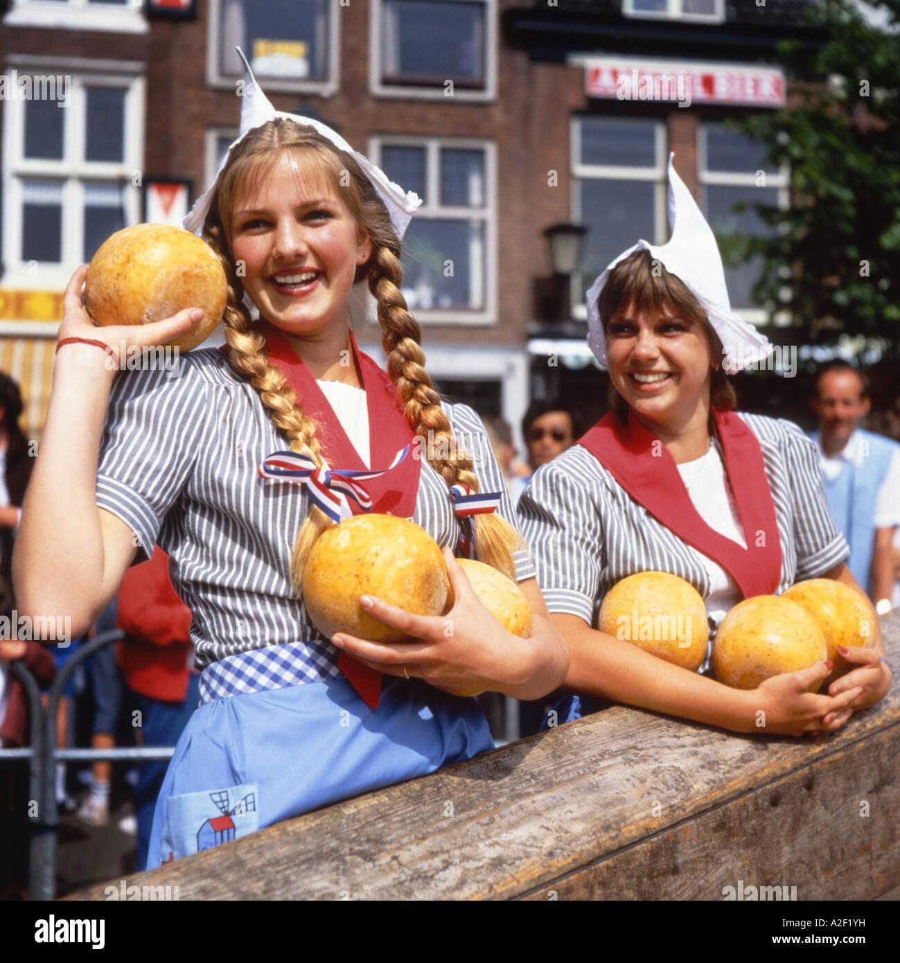 813b9d42ba4e Due ragazze Olandesi in abito tradizionale vendita di formaggi al mercato  di Alkmaar in Olanda