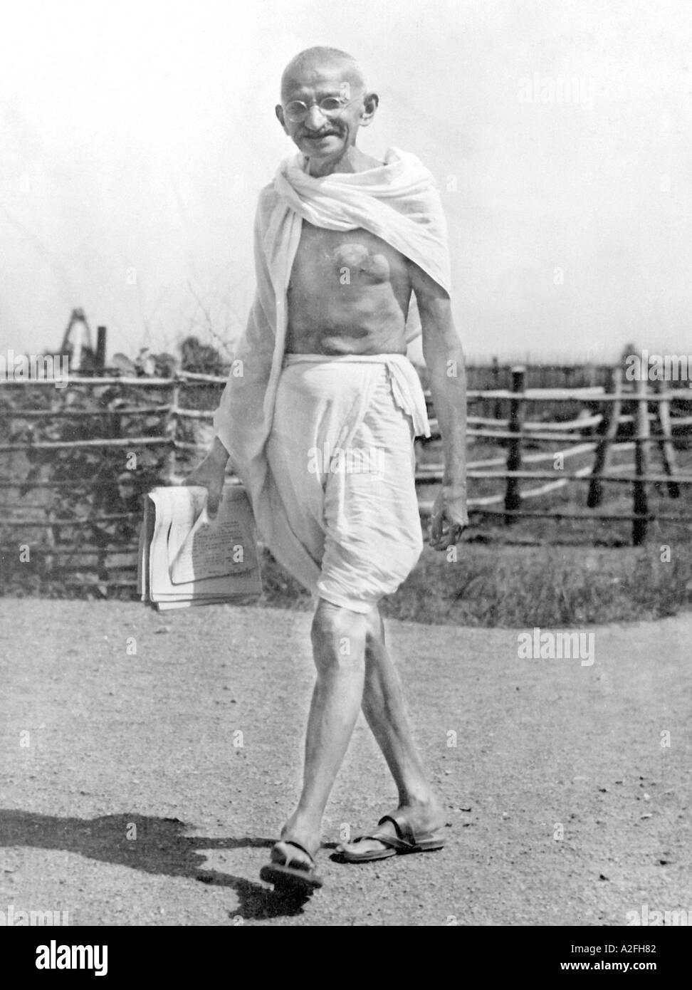 Il Mahatma Gandhi indossare dhoti con le carte in mano a piedi a Sevagram ashram in India Immagini Stock