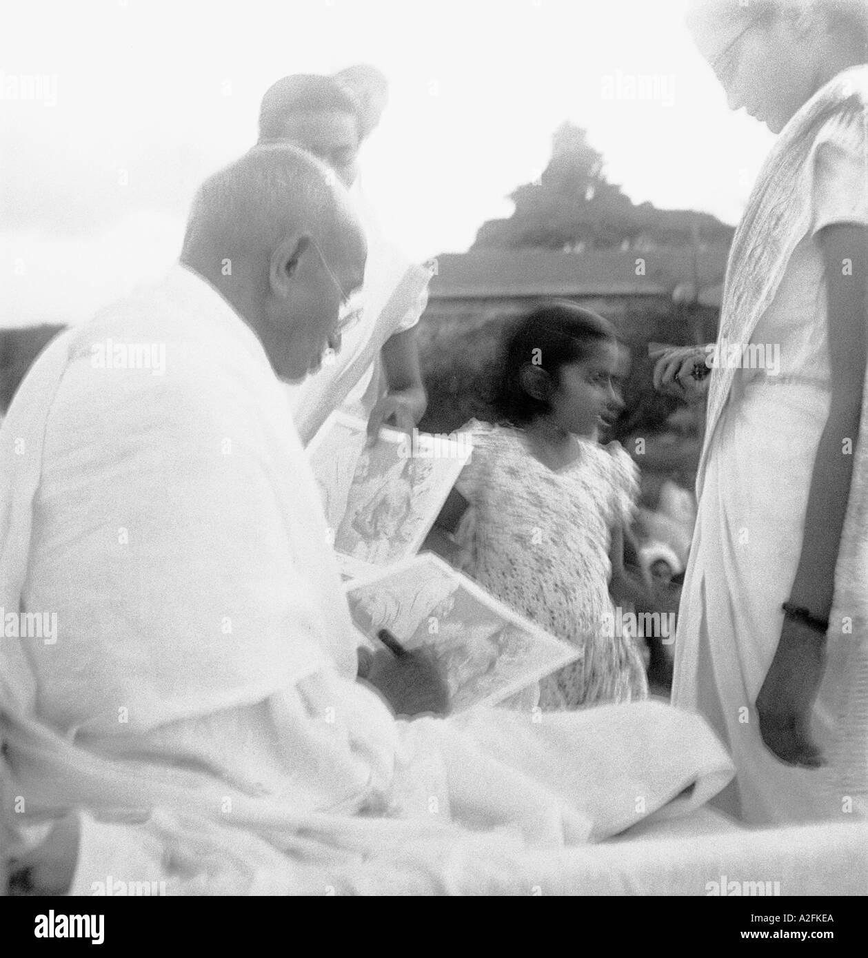 MKG33477 Mahatma Gandhi dando un autografo sul suo settantacinquesimo compleanno a Pune Maharashtra India 2 Ottobre 1944 Immagini Stock