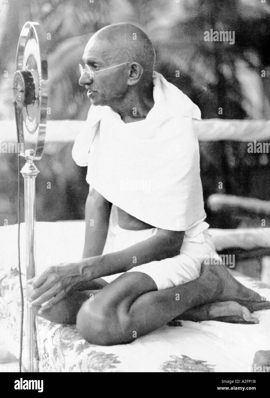 Il Mahatma Gandhi seduto e affrontare il microfono a un incontro pubblico a Mumbai Bombay Maharashtra India 28 Dicembre 1931 Immagini Stock
