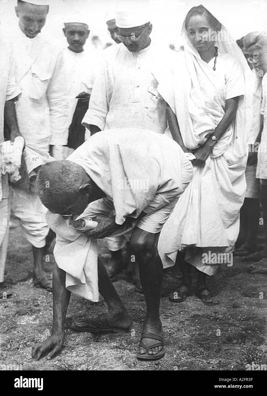 Il Mahatma Gandhi rompendo il diritto di sale sollevando un grumo di sale naturale a Dandi Gujarat India 6 aprile 1930 a 8-30 am Immagini Stock