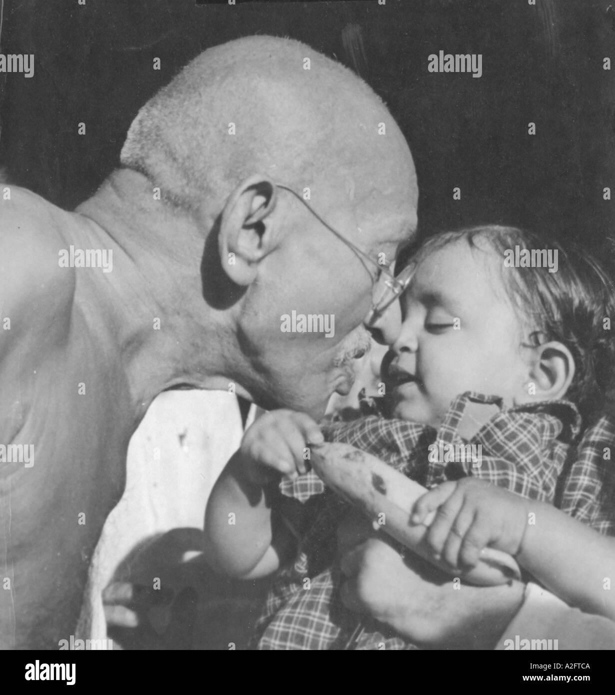 Il Mahatma Gandhi mostrando affetto e dando banana a Nandini nipote di Gandhi segretario Pyarelal Nayer Sewagram ashram in India 1944 - mkg 33185 Immagini Stock