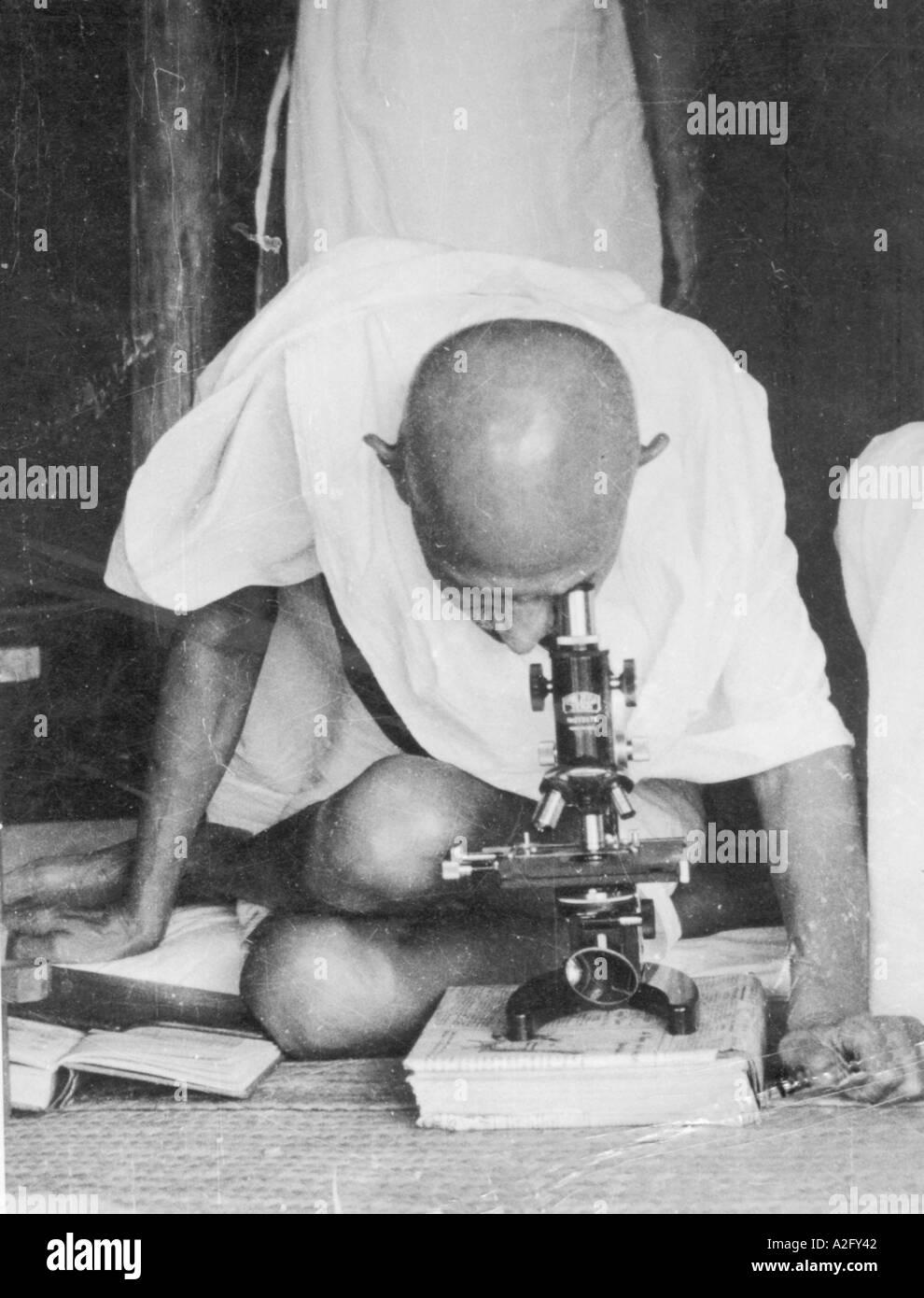 Il Mahatma Gandhi seduto gambe piegate guardando attraverso il microscopio e studiando la lebbra germi Sevagram ashram in India - Immagini Stock