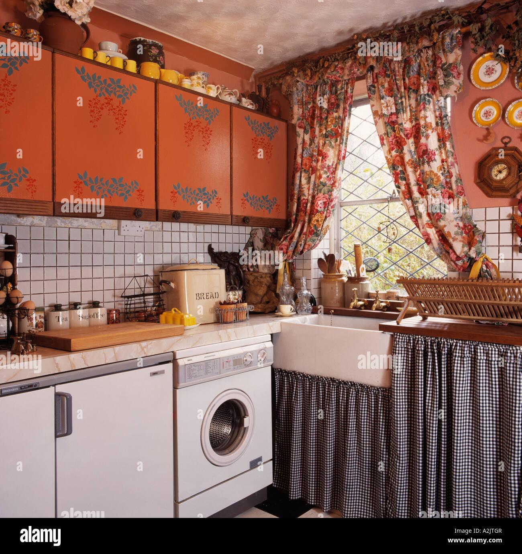 Impresse armadi e tende dai motivi floreali nella piccola cucina con ...