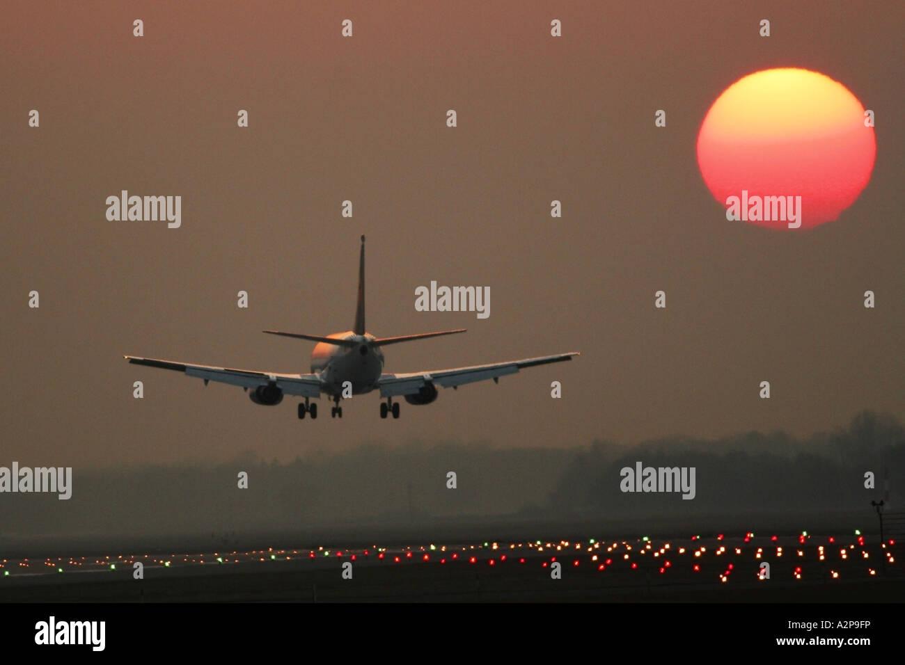 Aereo passeggeri di atterraggio su aeroporto di Monaco al tramonto, in Germania, in Baviera, Monaco di Baviera Immagini Stock