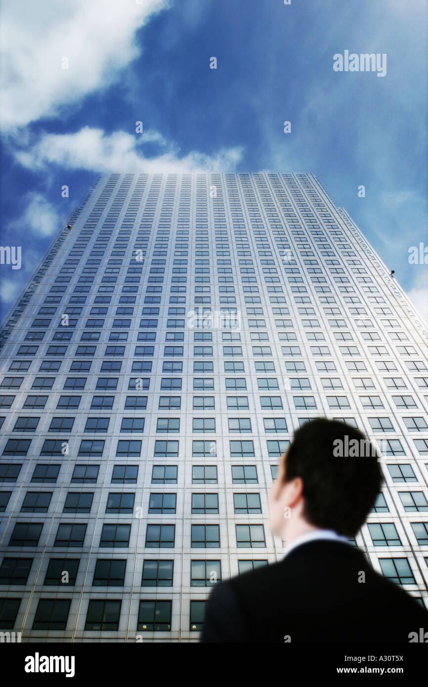 Il concetto di business di un uomo alla ricerca fino a un grattacielo Immagini Stock