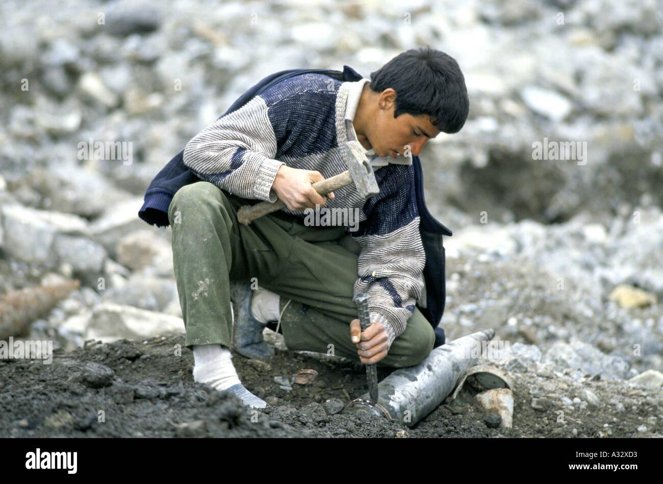 Colpo di Martello: un ragazzo cerca di rimuovere la banda di ottoni da una bomba live in, Diyana Molla, Kurdistan iracheno. Immagini Stock