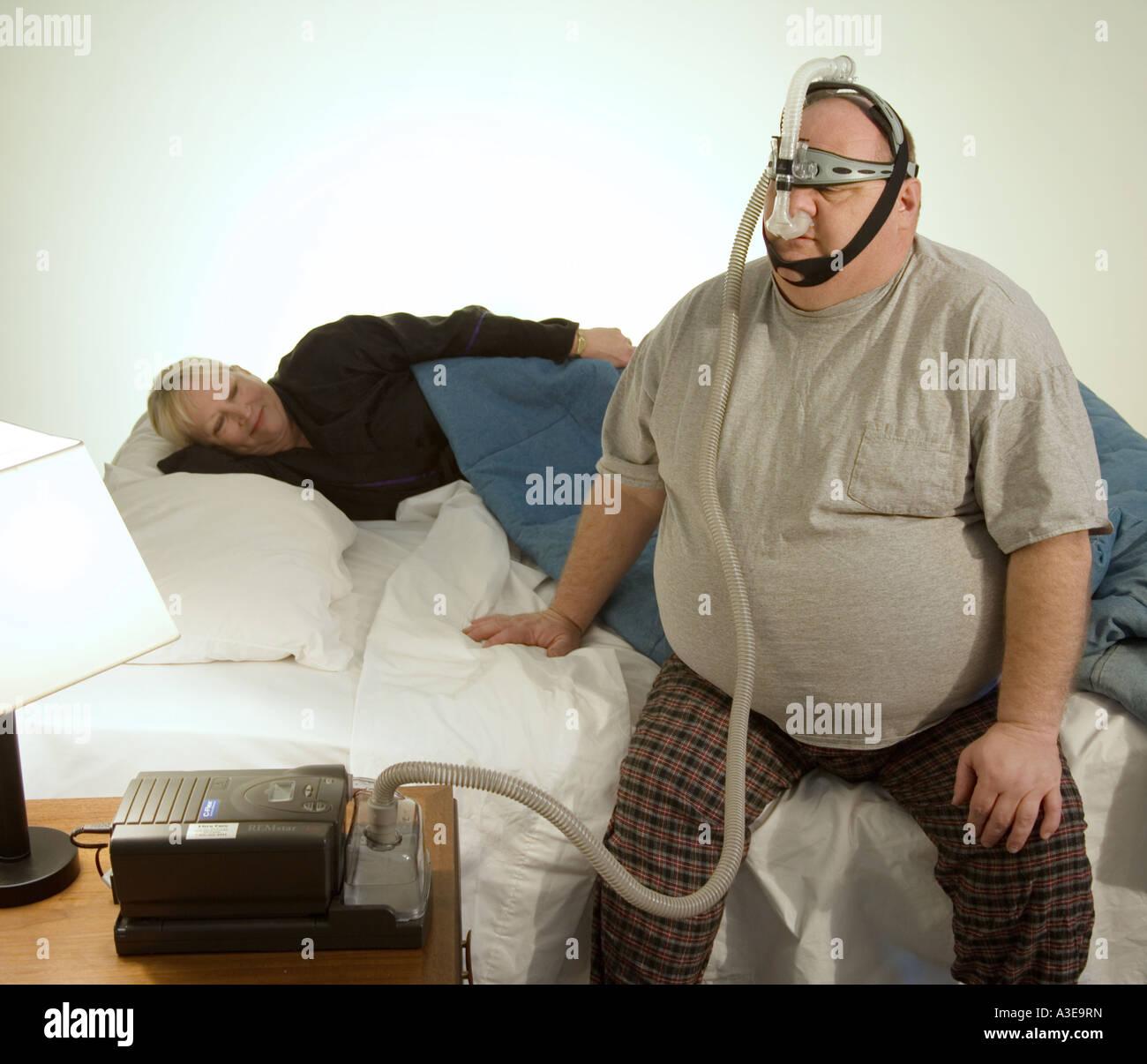 Uomo con apnea nel sonno problemi si prepara a letto come sua moglie cerca di dormire. La sua macchina CPAP è Immagini Stock