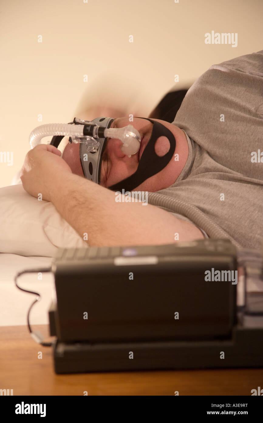 Il sovrappeso l'uomo cerca di dormire mentre indossa una macchina CPAP a letto. CPAP è pressione positiva Immagini Stock