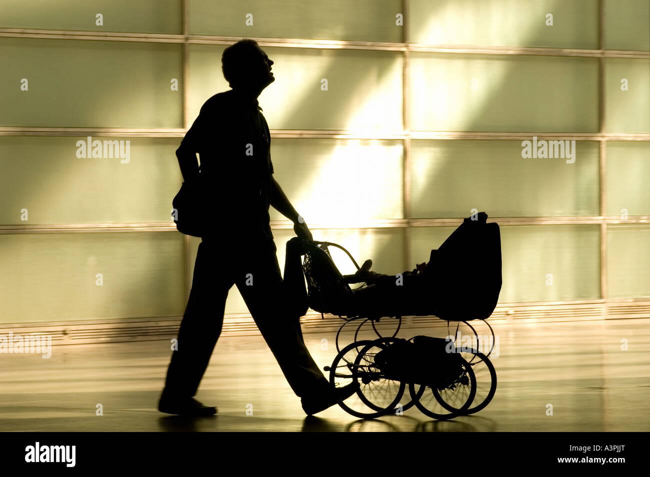 Silhouette di un uomo con un bambino passeggino Immagini Stock