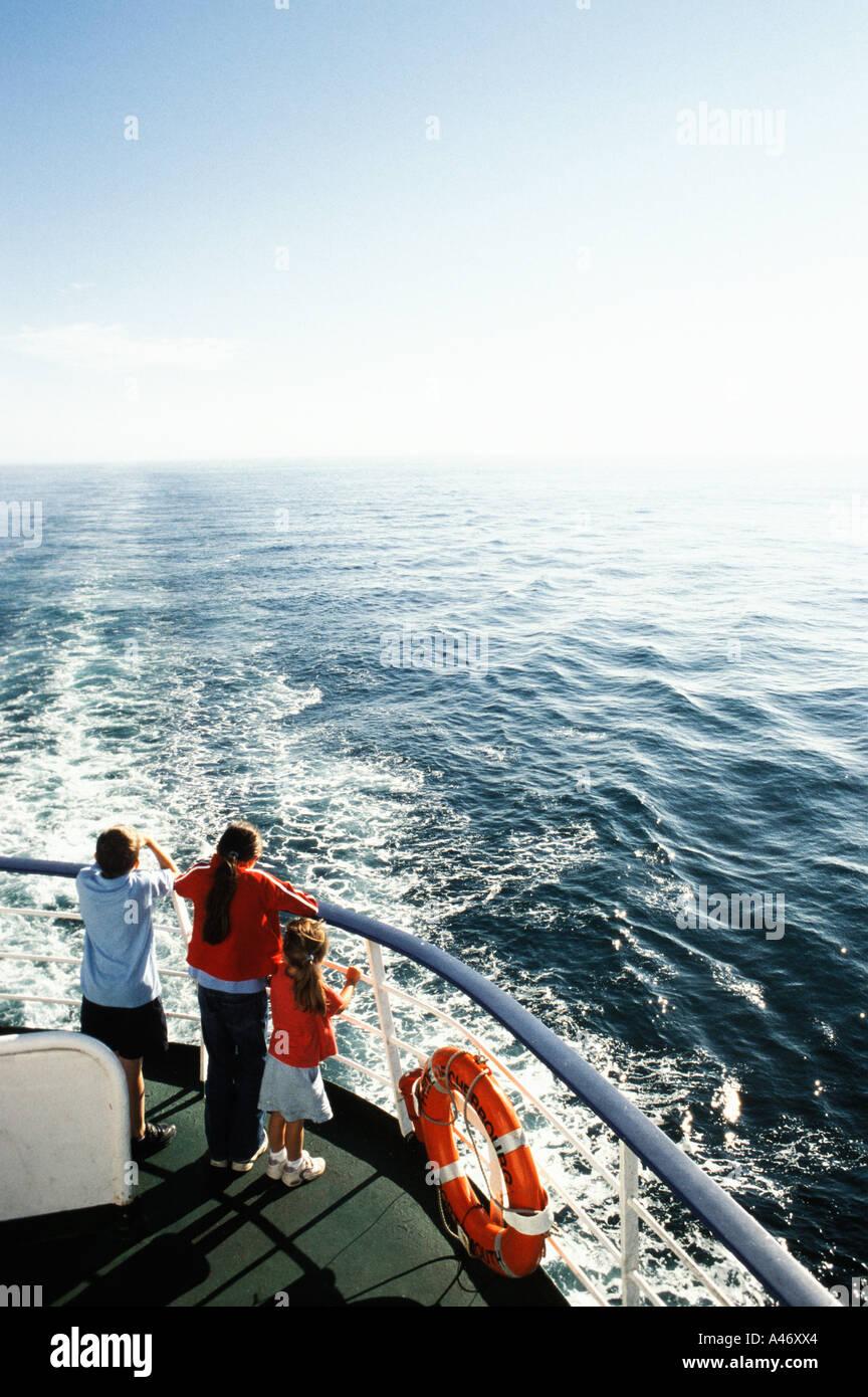 Tre bambini su una barca di traghetto Immagini Stock