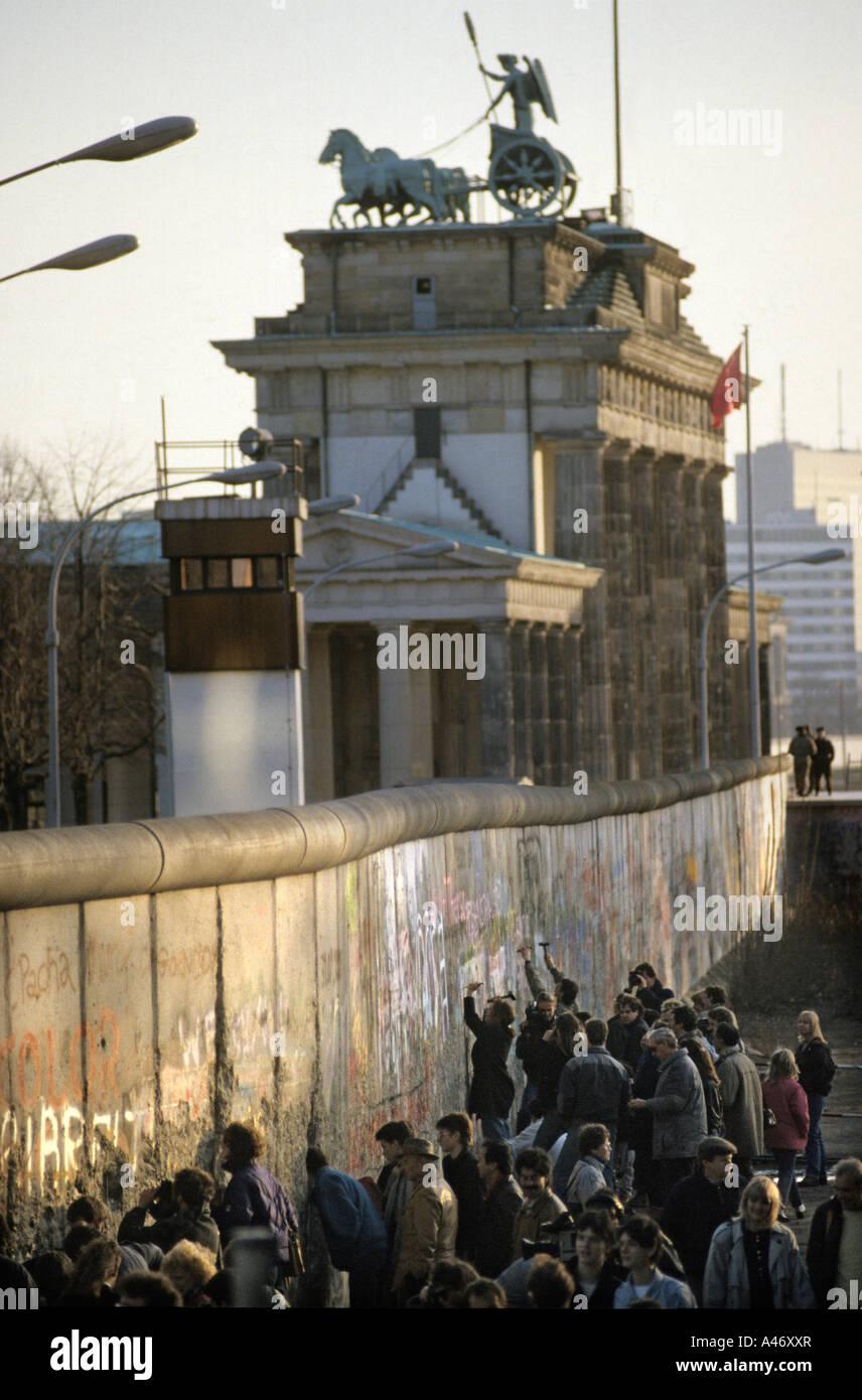 Caduta del muro di Berlino: persone scalpellatura parti fuori del muro alla porta di Brandeburgo (Mauerspecht), Immagini Stock