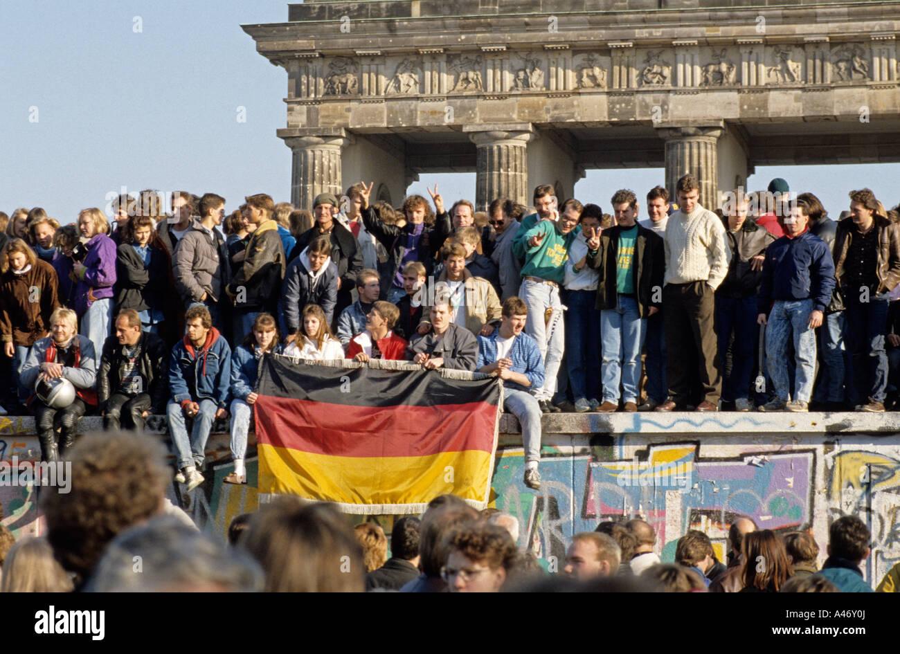 Caduta del muro di Berlino: persone da Berlino Ovest e Berlino Est salendo sulla parete presso la Porta di Brandeburgo, Immagini Stock