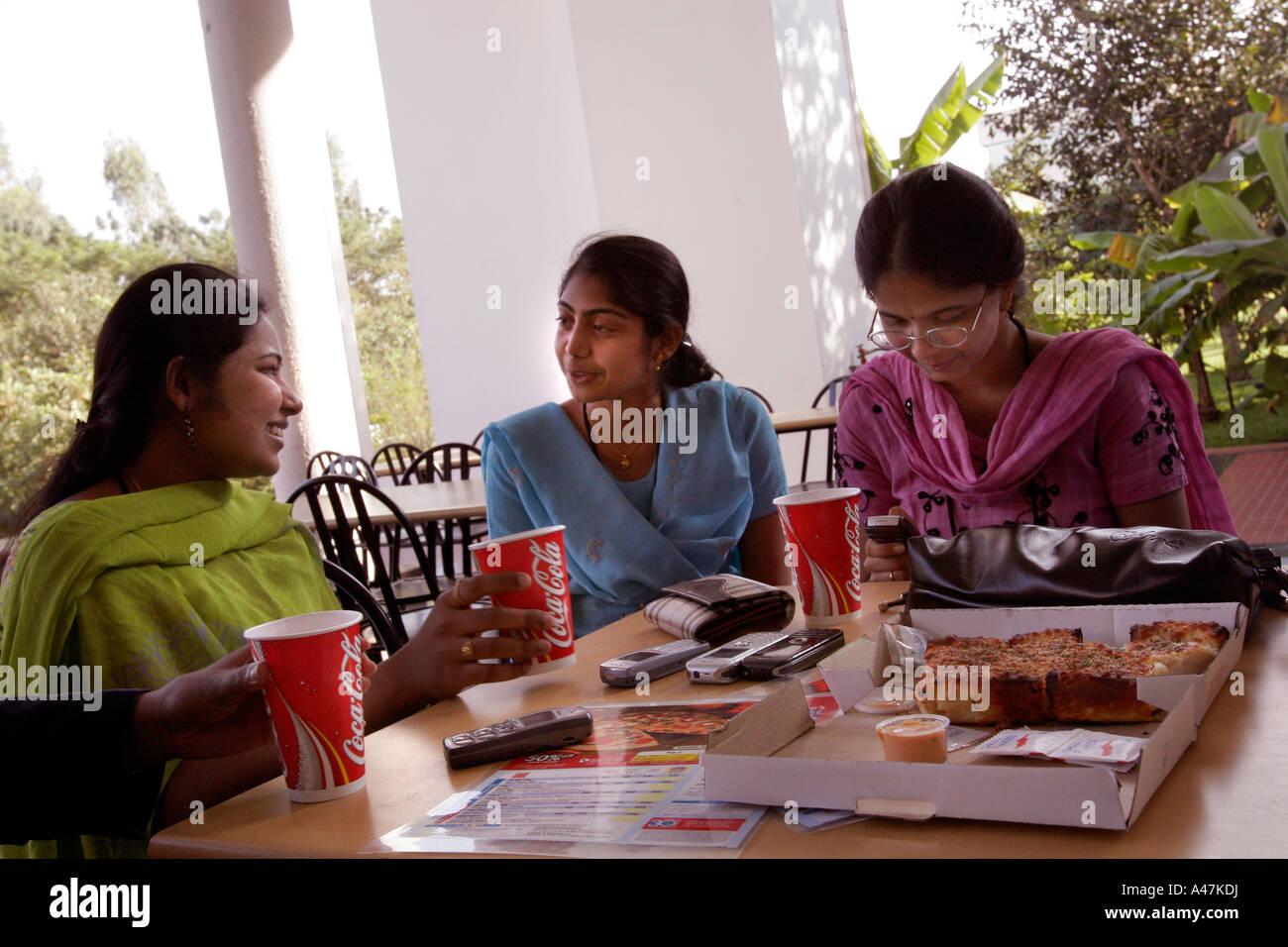 Giovani donne indiane che lavora nel settore IT per Infosys mangia fast food occidentali durante una pausa pranzo a Bangalore in India Foto Stock