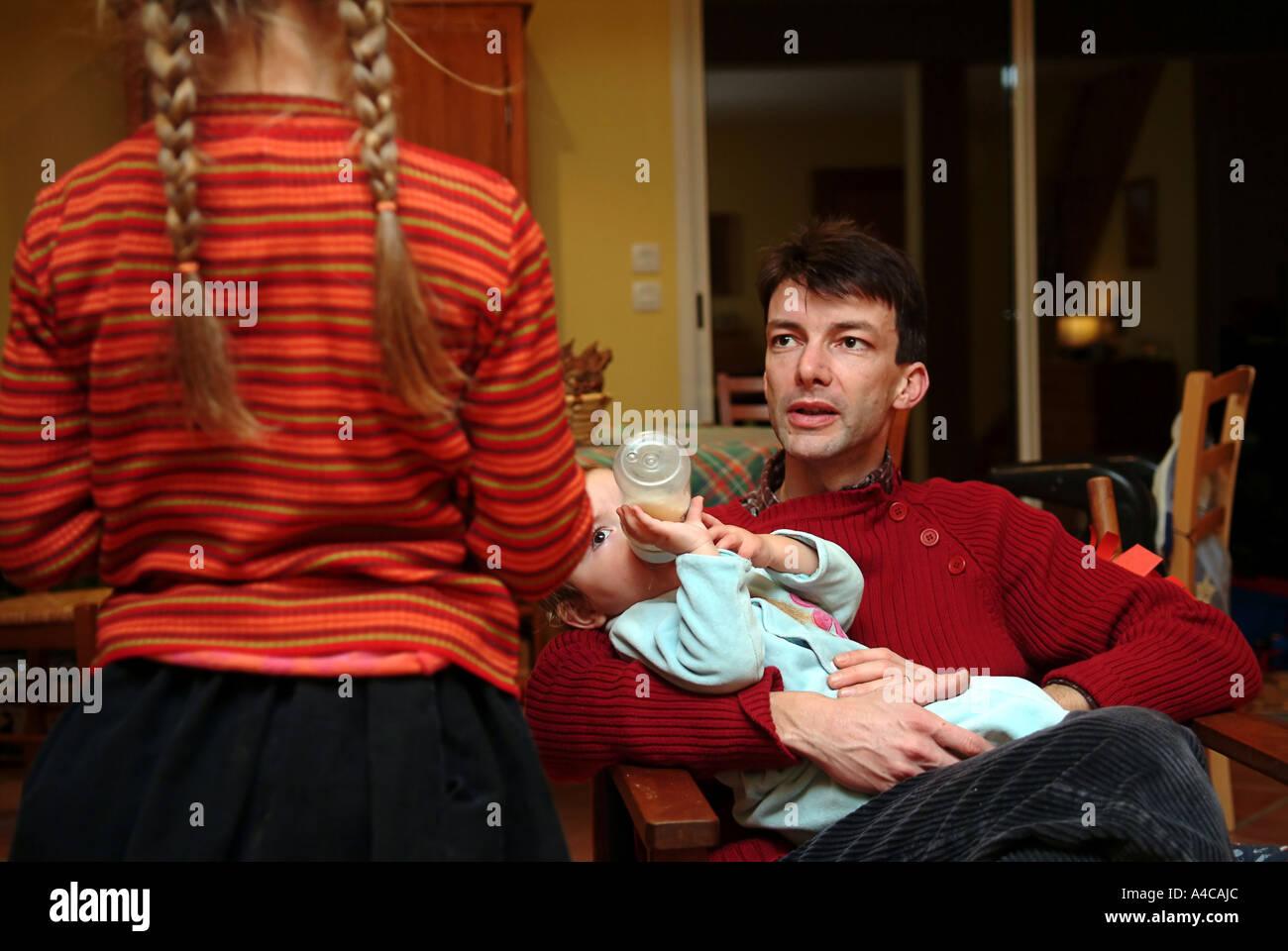 Papà è dando Charlotte il suo biberon Immagini Stock