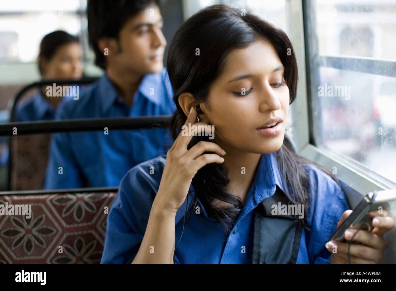 Studentessa ascoltando mp3 player sul bus Foto Stock