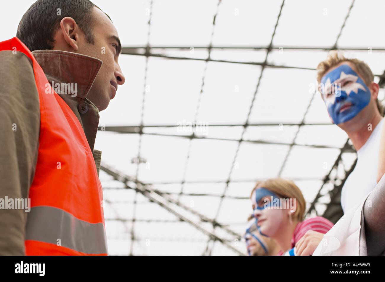 Steward guardando i tifosi di calcio Immagini Stock