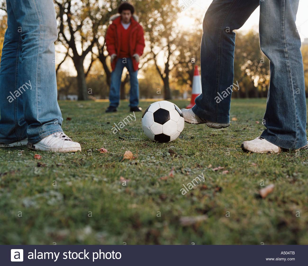 Gli uomini che giocano a calcio in posizione di parcheggio Immagini Stock